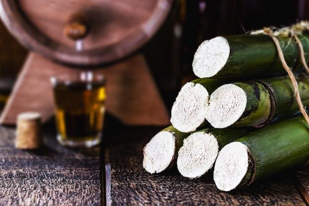 Trzcina cukrowa stosowana w napojach destylowanych, dno beczki i szkło z napojem alkoholowym