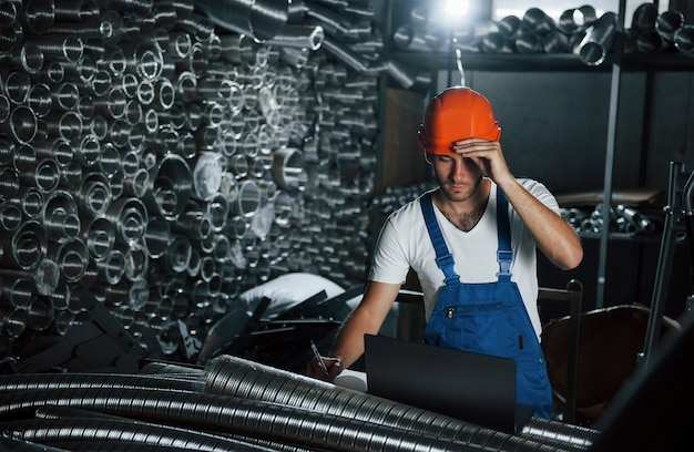 Trzeba być ostrożnym. mężczyzna w mundurze pracuje nad produkcją. nowoczesna technologia przemysłowa.