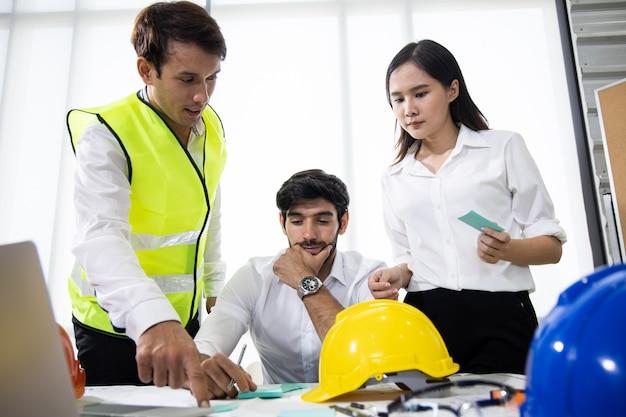 Trzech architektów w biurze i omawiających projekt.