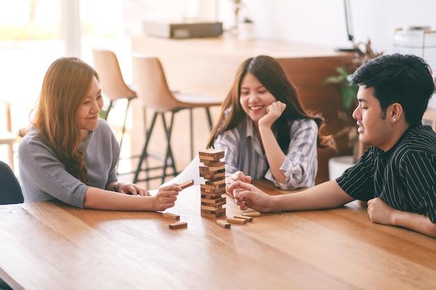 Trzech azjatyckich przyjaciół siedzących i grających w drewnianą grę tumble tower wraz z uczuciem szczęścia