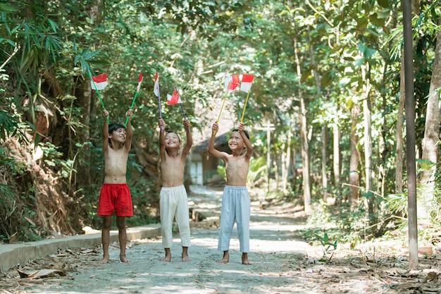 Trzech chłopców stojących trzymając małą czerwono-białą flagę i unosząc flagę