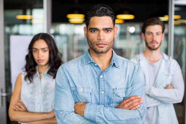 Trzech dyrektorów stojących z rękami skrzyżowanymi w biurze