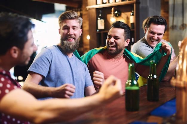 Trzech facetów ogląda zawody futbolu amerykańskiego