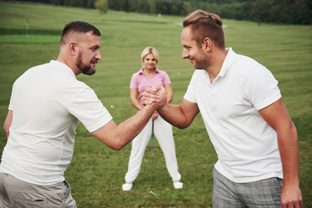 Trzech graczy gra na polu golfowym. zespół gratuluje sobie i podaje sobie ręce
