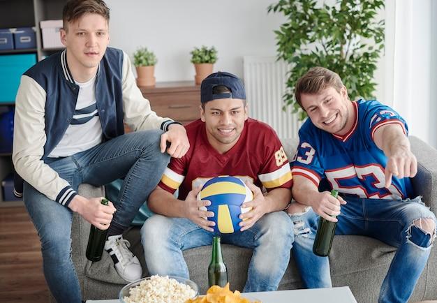 Trzech kolegów ogląda mecz siatkówki
