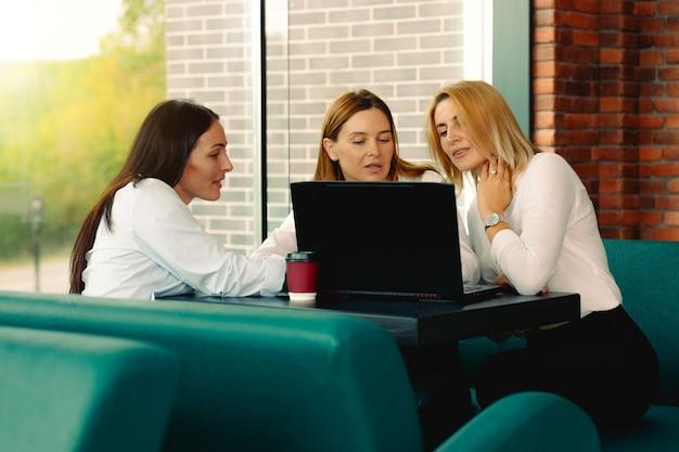 Trzech kolegów z nowoczesnego miejsca do pracy siedzi przy biurku z kawą. zespół: udany biznes zespół kobiety w biurze rozmawiając ze sobą patrząc na komputer.