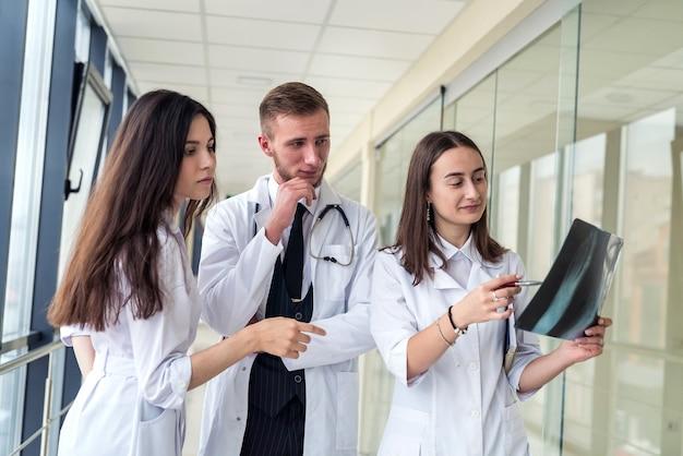 Trzech lekarzy omawia wyniki badań rentgenowskich w poradni. praca zespołowa