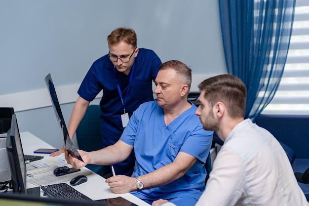 Trzech lekarzy patrząc na zdjęcia rentgenowskie w szpitalu. koncepcja neurochirurgii.