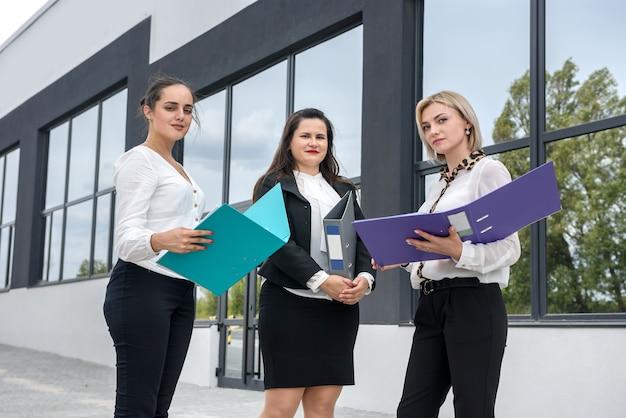 Trzech menedżerów z folderami pozującymi na zewnątrz biurowca