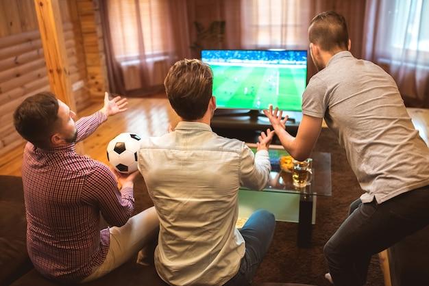 Trzech mężczyzn emocji ogląda piłkę nożną i gest