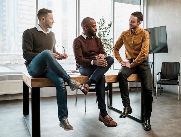 Trzech mężczyzn rozmawiających w biurze podczas spotkania