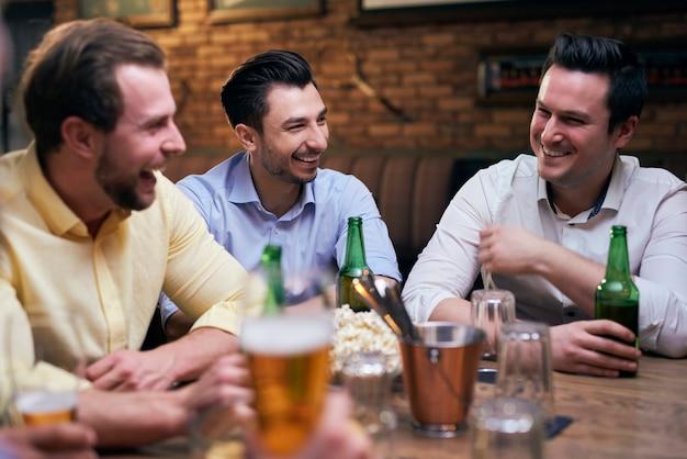 Trzech mężczyzn spędzających razem czas w pubie