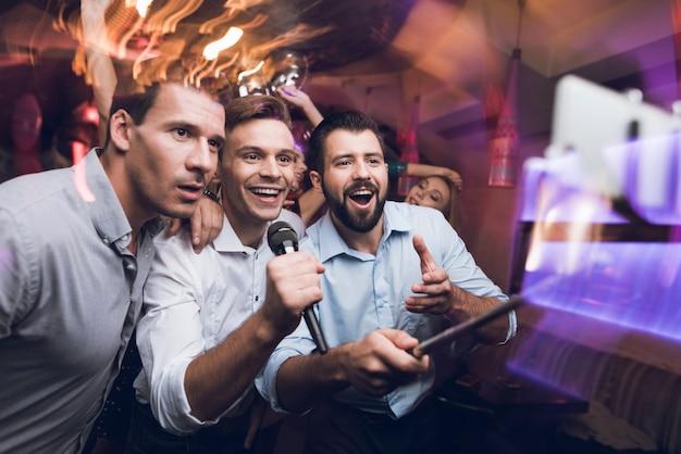 Trzech mężczyzn śpiewa w klubie karaoke. ludzie bawią się w nocnym klubie