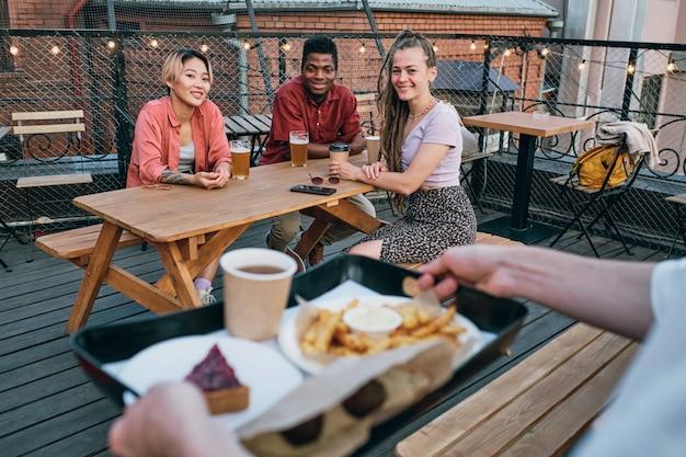Trzech międzykulturowych przyjaciół patrzących na kelnera niosącego tacę z jedzeniem i piciem