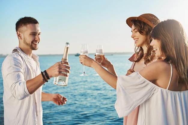 Trzech młodych atrakcyjnych i modnych ludzi stojących nad morzem i pijących z szerokim uśmiechem, rozmawiających o czymś. koledzy spędzający wolny czas na imprezie zorganizowanej przez ich firmę.