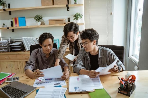 Trzech młodych azjatyckich biznesmenów na czacie o swoim produkcie