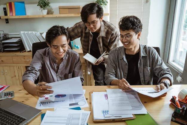 Trzech młodych azjatyckich pracowników rozmawiających o swoim produkcie