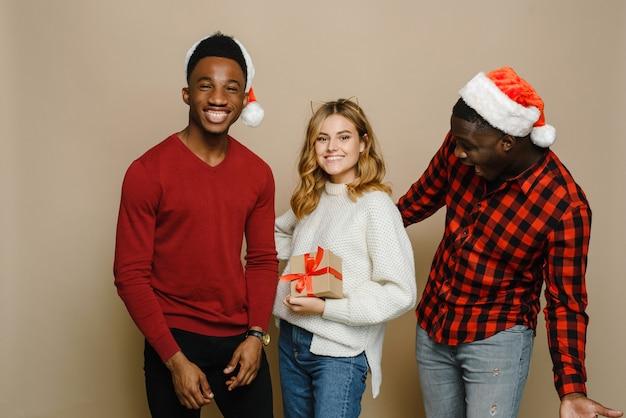 Trzech młodych i pięknych przyjaciół różnych narodowości w czapkach mikołajowych cieszy się niespodzianką i pudełkiem prezentowym.