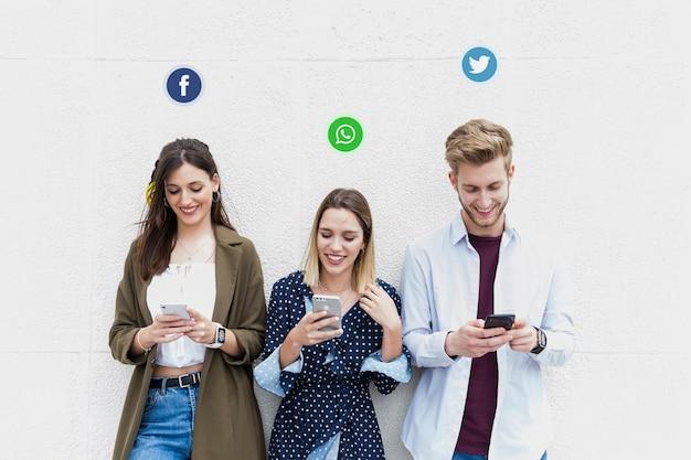 Trzech młodych ludzi korzystających z różnych serwisów społecznościowych na swoim telefonie komórkowym