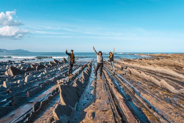 Trzech młodych ludzi na wybrzeżu sakoneta pozdrawiając