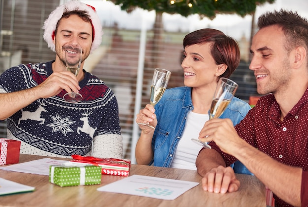 Trzech młodych ludzi pije szampana w biurze