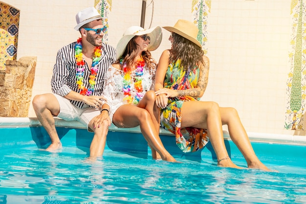 Trzech młodych ludzi, siedzących na brzegu basenu, uśmiechniętych