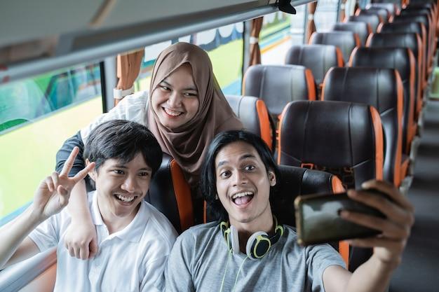 Trzech młodych ludzi uśmiecha się i pozuje do aparatu w telefonie, robiąc razem selfie w autobusie