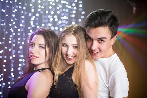 Trzech młodych mężczyzn i dwie kobiety bawią się w nocnym klubie na imprezie