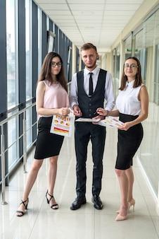Trzech młodych partnerów biznesowych szczęśliwy omawianie umowy lub raportu stojąc w korytarzu biura.