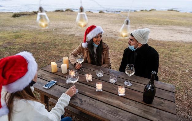 Trzech młodych pięknych ludzi w kapeluszu świętego mikołaja siedzi na zewnątrz, pijąc szampana z okazji bożego narodzenia