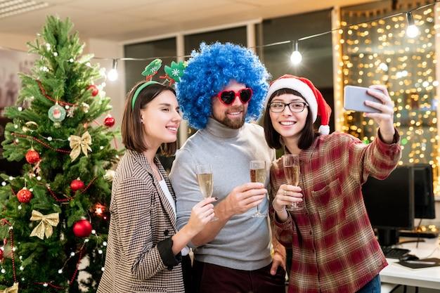 Trzech młodych pracowników biurowych z fletami szampana podczas robienia selfie w boże narodzenie