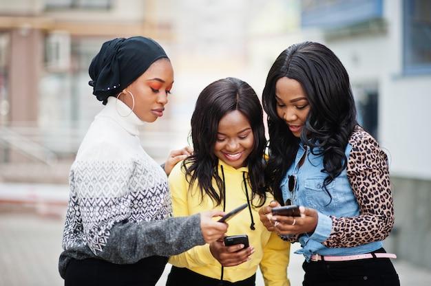 Trzech młodych przyjaciół afroamerykanów kolegium kobieta z telefonów komórkowych.