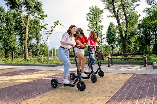 Trzech młodych przyjaciół dziewczyna na wakacjach zabawy jazdy skuterem elektrycznym