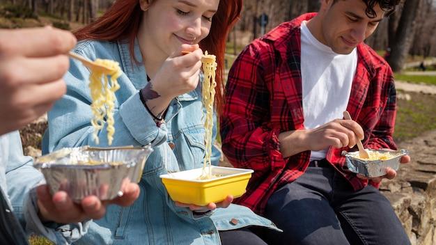 Trzech młodych przyjaciół jedzących makaron w parku