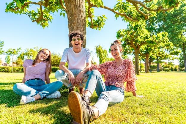 Trzech młodych różnorodnych przyjaciół odpoczynku na polu zielonego parku uśmiecha się patrząc na kamery na portret. studenci z pokolenia z spędzają czas na łonie natury, przełamując rutynę miejskiego życia. przyjaźń nie ma znaczenia