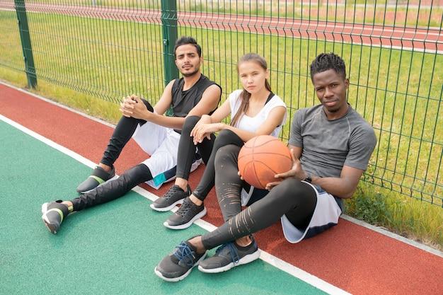 Trzech młodych sportowców w odzieży sportowej siedzi na boisku do koszykówki na świeżym powietrzu przy siatce i odpoczywa po meczu