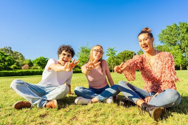 Trzech młodych studentów najlepszych przyjaciół siedzi na trawie w parku miejskim pokazując znak zwycięstwa dwoma palcami patrząc na kamery. pojęcie jedności i solidarności w wieku młodzieńczym. szczęśliwy gen z uśmiechający się w naturze