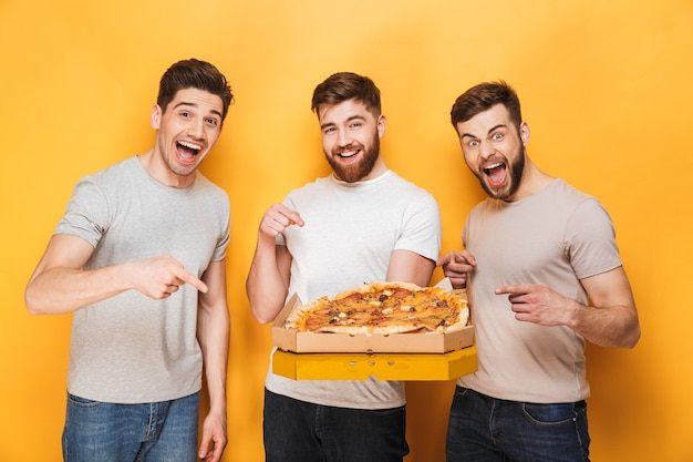 Trzech młodych szczęśliwych mężczyzn posiadających dużą pizzę