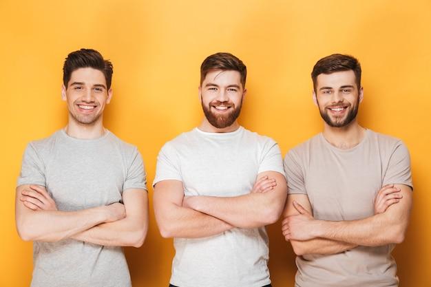 Trzech młodych uśmiechniętych mężczyzn stojących z założonymi rękoma