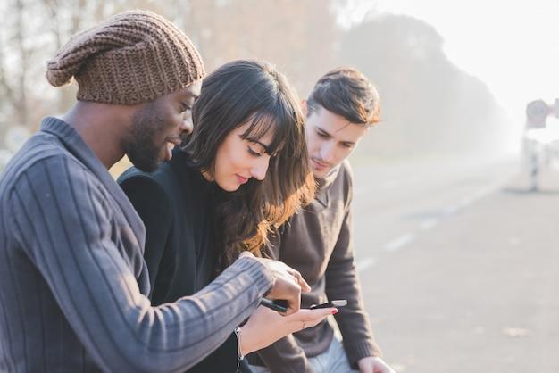 Trzech młodych wieloetnicznych przyjaciół na zewnątrz za pomocą smartfona