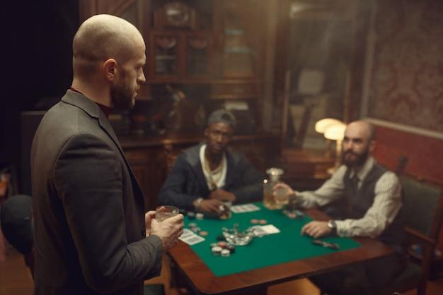 Trzech pokerzystów siedzących przy stole z whisky i cygarami
