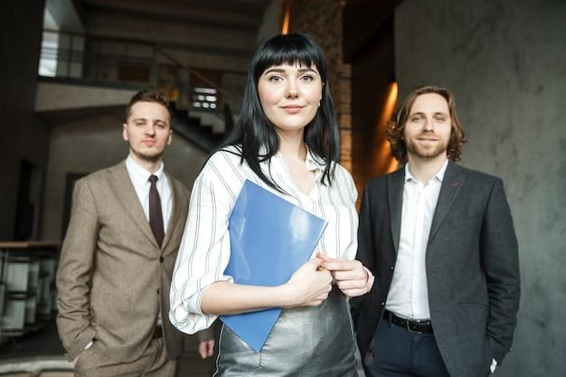 Trzech pracowników biurowych stoi razem i patrzy w kamerę