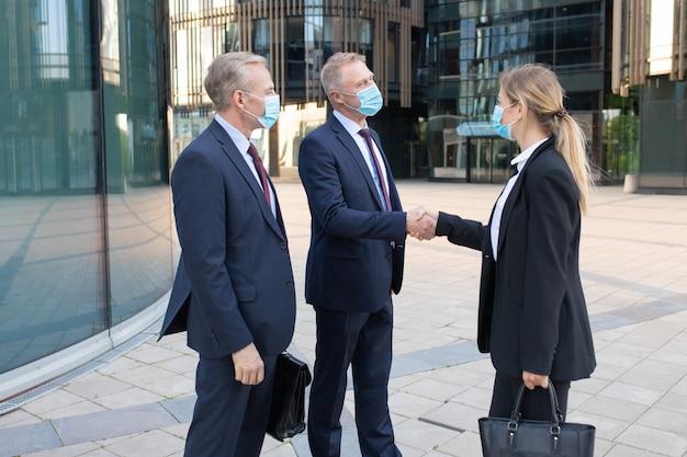 Trzech pracowników biurowych w maskach na twarz robi interesy lub pozdrowienia. profesjonalny sukces bizneswoman i biznesmeni stojący na zewnątrz i uścisk dłoni. koncepcja negocjacji, ochrony i partnerstwa