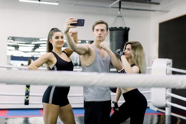 Trzech profesjonalnych bokserów i trenerów fitness robi selfie, stojąc na środku ringu