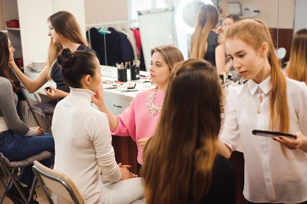 Trzech profesjonalnych wizażystów pracuje z pięknymi młodymi kobietami. szkoła makijażu zawodowego.