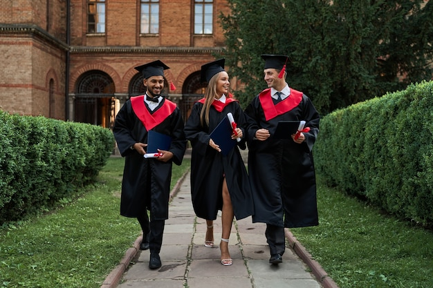 Trzech przyjaciół absolwentów w sukniach dyplomowych spacerujących po kampusie.