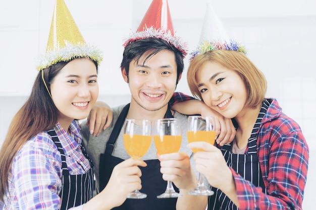 Trzech przyjaciół ciesząc się ze szkła party, picie koktajlu sok pomarańczowy razem