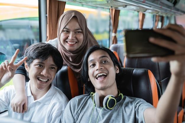 Trzech przyjaciół uśmiecha się i pozuje przed aparatem w telefonie komórkowym podczas wspólnego robienia selfie w autobusie