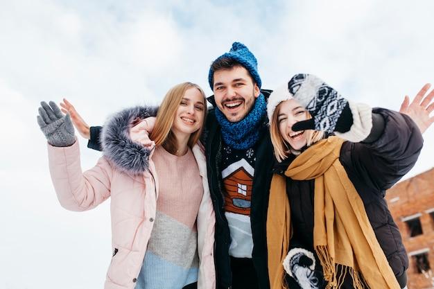 Trzech przyjaciół w zimowe ubrania macha rękami na zewnątrz