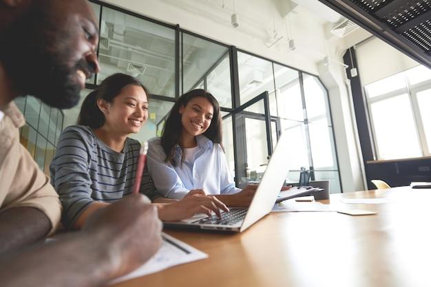 Trzech przyjaznych współpracowników patrzących na ekran komputera